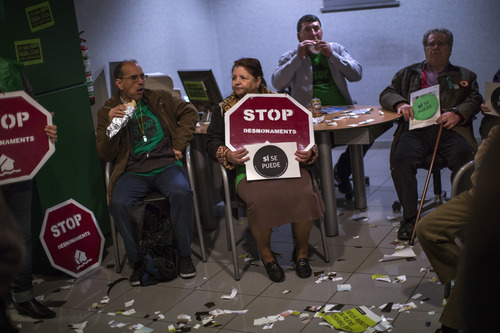 Members of the Mortgage Victims' Platform (PAH) eat their sandwiches as they occupy a Bankia bank branch as part of a protest to support neighbors who are facing the evictions process in Barcelona, Spain, Friday, April 5, 2013. With 26 percent unemployment, Spain is struggling to emerge from its second recession in just over three years. Spain's borrowing costs have dropped in recent months with investors less wary since European authorities announced the country would be helped, if needed, to handle its debt. (AP Photo/Emilio Morenatti)