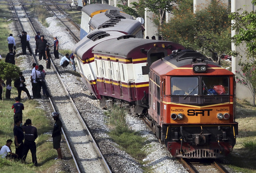 Officials from the State Railway of Thailand (SRT) wait for orders outside a train which was derailed before entering Bangkok station in Bangkok, Thailand, Friday, April 5, 2013. Three people were injured in the accident which officials said is still under investigation. (AP Photo/Apichart Weerawong)