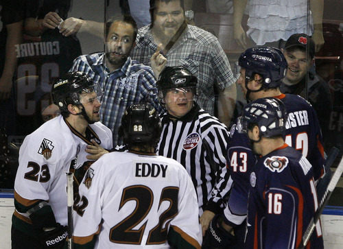 """Scott Sommerdorf      The Salt Lake Tribune """"Don't make me come over there."""" Grizzlies fans give Ontario Reign defensemean Matt Register some lip as the referee separates fighting players during second period play. After a scoreless second period, the Utah Grizzlies led the Ontario Reign 1-0 on forward Chris Donovan's first period penalty shot goal in Game 3 of the ECHL playoffs at the Maverick Center, Friday, April 5, 2013."""
