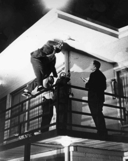 FILE - Memphis detectives climb on a rail outside the room of Dr. Martin Luther King at the Lorraine Motel, Memphis, on April 4, 1968, searching for clues.  The civil rights leader was standing on the balcony of the Lorraine Motel when he was killed by a rifle bullet.  James Earl Ray pleaded guilty to the killing and was sentenced to 99 years in prison. He died in prison in 1998. (AP Photo)