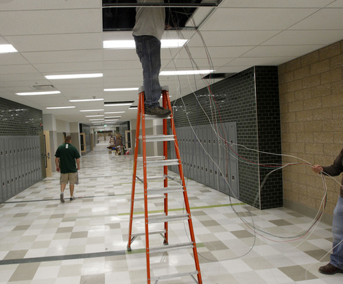 Al Hartmann  |  The Salt Lake Tribune Electrical worker finishes wiring in hallway of new Olypus HIgh School on Tuesday April 2 as teachers move in.