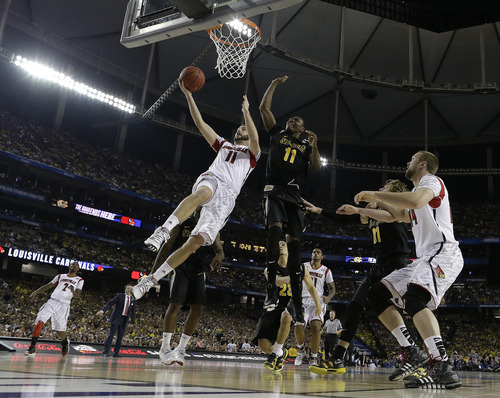 Louisville's Luke Hancock (11) shoots against Wichita State's Cleanthony Early (11) during the second half of the NCAA Final Four tournament college basketball semifinal game Saturday, April 6, 2013, in Atlanta. (AP Photo/David J. Phillip)