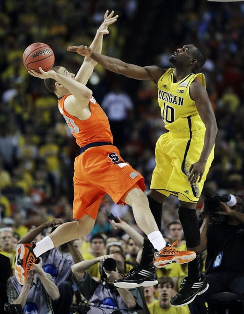 Syracuse's Brandon Triche (20) shoots against Michigan's Tim Hardaway Jr. (10) during the first half of an NCAA Final Four tournament college basketball semifinal game Saturday, April 6, 2013, in Atlanta. (AP Photo/David J. Phillip)