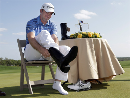 Martin Laird, of Scotland, slides into a pair of boots he received for winning  the Texas Open golf tournament, Sunday, April 7, 2013, in San Antonio.  (AP Photo/Eric Gay)
