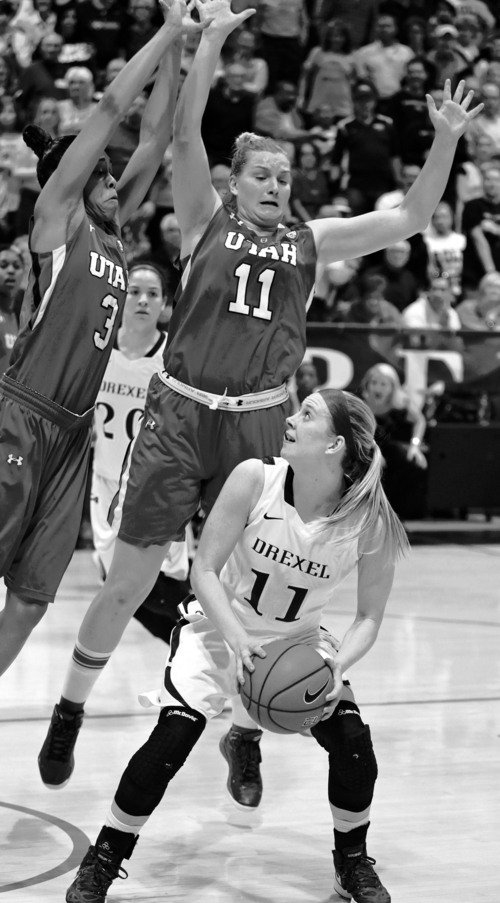 Drexel's Hollie Mershon, right, fakes Utah's Iwalani Rodrigues, left, and Taryn Wicijowski, center, before splitting the defenders and scoring with about 20 seconds left during the Women's NIT championship basketball game Saturday, April 6, 2013, in Philadelphia. Drexel defeated Utah 46-43. (AP Photo/Philadelphia Inquirer, Charles Fox) TV OUT  MAGS OUT