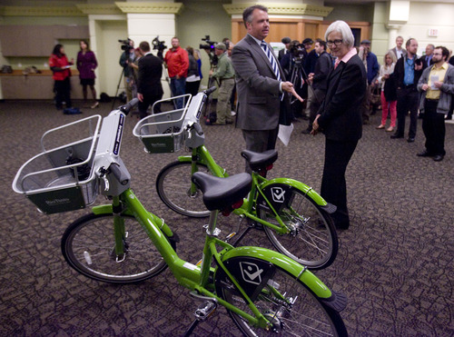 Kim Raff  |  The Salt Lake Tribune (left) Jason Mathis, Downtown Alliance executive director, and Patricia Richards, SelectHealth president and CEO, walk past GREENbikes on display during the launch event for the GREENbike SLC bicycle-sharing project at the Wells Fargo building in Salt Lake City on Monday April 8, 2013. The program is a partnership between Salt Lake City, the Downtown Alliance, the Salt Lake Chamber and SelectHealth. The program will start with 100 GREENbikes and 10 stations around downtown.