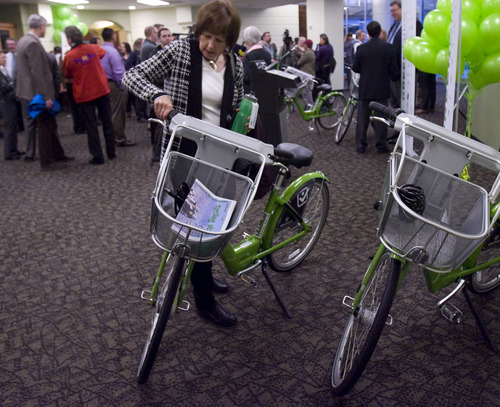 Kim Raff  |  The Salt Lake Tribune Downtown Alliance board member Peggy Lander checks out the new GREENbikes that are displayed during the launch event for the GREENbike SLC bicycle-sharing project at the Wells Fargo building in Salt Lake City on Monday April 8, 2013. The program is a partnership between Salt Lake City, the Downtown Alliance, the Salt Lake Chamber and SelectHealth. The program will start with 100 GREENbikes and 10 stations around downtown.