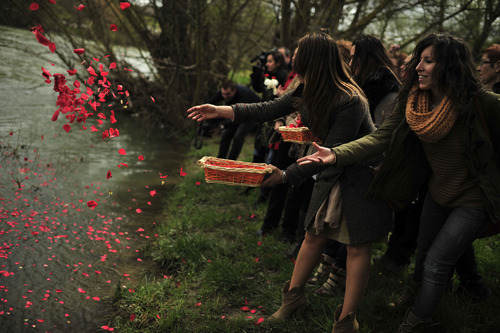 Female gypsy people throw flower petals into the Arga River in honor of their ancestors on the Day of the Gypsy, in Pamplona northern Spain, on Monday, April 8, 2013.(AP Photo/Alvaro Barrientos)