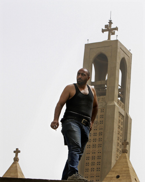 An Egyptian Christian man stands on the wall of the Coptic cathedral in Cairo, Egypt, Monday, April 8, 2013. A senior Egyptian health ministry official says the death toll in clashes between Muslims and Christians in Cairo has risen to two. Dozens of people were injured. (AP Photo/Amr Nabil)