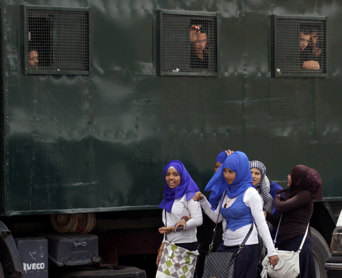 Egyptian anti-riot soldiers on alert, look as girls walking past their vehicle, near the Coptic cathedral in Cairo, Egypt, Monday, April 8, 2013. A senior Egyptian health ministry official says the death toll in clashes between Muslims and Christians in Cairo has risen to two. Dozens of people were injured. (AP Photo/Amr Nabil)