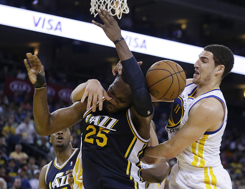 Utah Jazz's Al Jefferson (25) and Golden State Warriors' Klay Thompson (11) fight for a rebound during the second half of an NBA basketball game, Sunday, April 7, 2013, in Oakland, Calif. (AP Photo/Ben Margot)