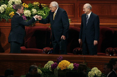 Scott Sommerdorf   |  The Salt Lake Tribune Elder David A. Bednar, left, fist bumps Elder L. Tom Perry with the empty chair of Elder Boyd K. Packer between them at the end of the afternoon session of the 183rd LDS General Conference, Sunday, April 7, 2013. Elder M. Russell Nelson is at the far right. Packer did not attend Sunday.