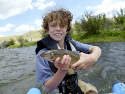 Ten-year-old Bryce Fehlig with a  whitefish he caught on his fly rod while fishing the Madison River in Montana.
