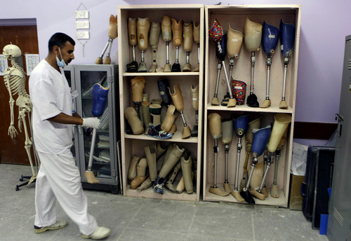 An orthotist looks at prosthetic legs at the prosthetic limbs hospital in Baghdad, Iraq, Tuesday, April 9, 2013. The toppling of the longtime dictator Saddam Hussein, 16 feet bronze statue remains a potent symbol that has divided Iraqis ever since: liberation for Shiites and Kurds, a loss for some Sunnis and grief among almost everybody over the years of death, destruction and occupation that followed the fall of the capital to U.S. forces on April 9, 2003. (AP Photo/ Khalid Mohammed)