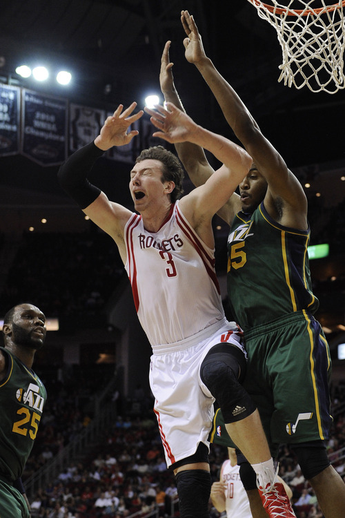 Houston Rockets' Omer Asik (3) collides with Utah Jazz's Derrick Favors (15) in the first half of an NBA basketball game Wednesday, March 20, 2013, in Houston. (AP Photo/Pat Sullivan)
