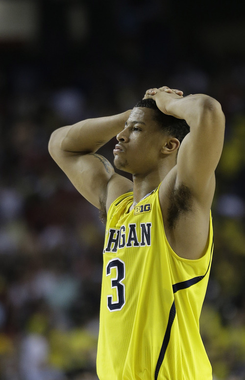 Michigan guard Trey Burke (3) walks off the court as Louisville celebrate their win during the second half of the NCAA Final Four tournament college basketball championship game Monday, April 8, 2013, in Atlanta. Louisville won 82-76.  (AP Photo/John Bazemore)
