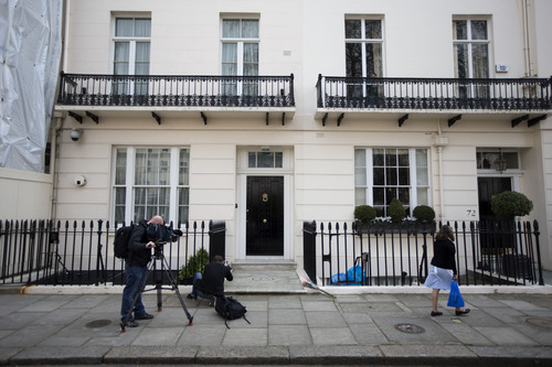 """Members of the media film and photograph floral tributes laid outside the home of the late former British Prime Minister Margaret Thatcher in London, Monday, April 8, 2013. Margaret Thatcher, the combative """"Iron Lady"""" who infuriated European allies, found a fellow believer in Ronald Reagan and transformed her country by a ruthless dedication to free markets in 11 bruising years as prime minister. She died Monday at age 87.  (AP Photo/Matt Dunham)"""