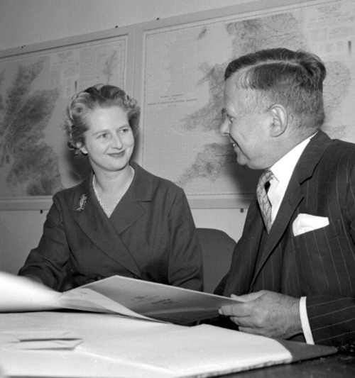 FILE - In a Oct. 12, 1961 file photo, Mrs Margaret Thatcher, the newly appointed Joint Parliamentary Secretary at the Ministry of Pensions and national Insurance, talks with the Minister John Boyd Carpenter, as she begins her new job at the Ministry, in London. Thatcher's former spokesman, Tim Bell, said that the former British prime minister died Monday morning, April 8, 2013, of a stroke.  She was 87. (AP Photo/Bob Dear, File)