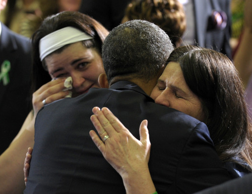 President Barack Obama hugs Newtown family members after speaking at the University of Hartford in Hartford, Conn., Monday, April 8, 2013. Obama said that lawmakers have an obligation to the children killed and other victims of gun violence to act on his proposals.  (AP Photo/Susan Walsh)