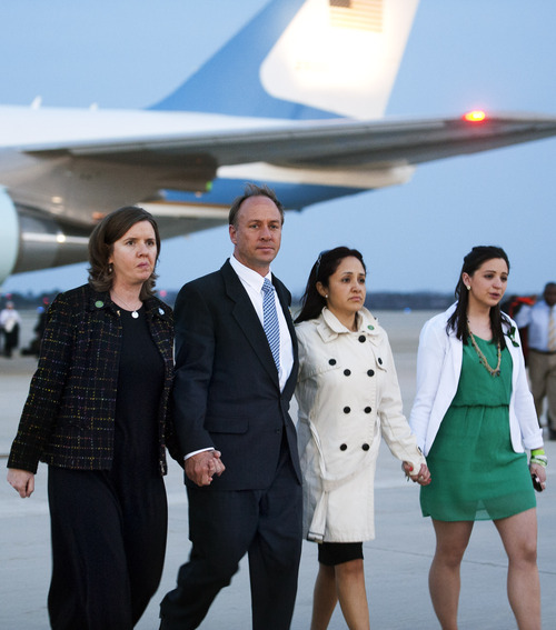 Mark and Jackie Barden, parents of 7 year-old Daniel, left, walk with Nelba Marquez-Greene, mother of 6 year-old Ana, center, and an unidentified woman from Air Force One to waiting White House vans after landing at Andrews Air Force Base, Md., Monday, April 8, 2013 with President Barack Obama and other families who lost relatives in the Sandy Hook Elementary School shooting. Obama was returning from Hartford, Conn., where he spoke at the University of Hartford, near the state capitol where last week the governor signed into law some of the nation's strictest gun control laws. (AP Photo/Cliff Owen)
