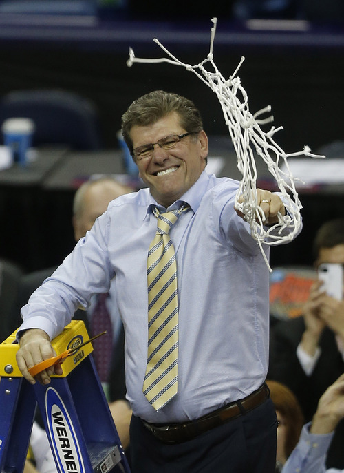 Connecticut head coach Geno Auriemma celebrates after defeating Louisville 93-60 in the national championship game of the women's Final Four of the NCAA college basketball tournament, Tuesday, April 9, 2013, in New Orleans.  (AP Photo/Bill Haber)