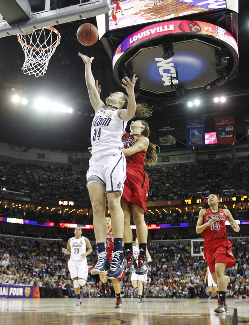Connecticut guard Kelly Faris (34) goes up for a shot against Louisville guard Jude Schimmel (22) during the second half of the national championship game of the women's Final Four of the NCAA college basketball tournament, Tuesday, April 9, 2013, in New Orleans. (AP Photo/Gerald Herbert)