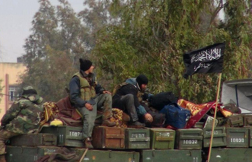 "FILE - In this Friday, Jan. 11, 2013 file citizen journalism image provided by Edlib News Network, ENN, which has been authenticated based on its contents and other AP reporting, shows rebels from al-Qaida affiliated Jabhat al-Nusra, as they sit on a truck full of ammunition, at Taftanaz air base,  that was captured by the rebels, in Idlib province, northern Syria.  Al-Qaida's branch in Iraq said it has merged with Syria's extremist Jabhat al-Nusra, a move that shows the rising confidence of radicals within the Syrian rebel movement and is likely to trigger renewed fears among its international backers. Arabic on the flag, right, reads, ""There is no God only God and Mohamad his prophet, Jabhat al-Nusra."" (AP Photo/Edlib News Network ENN, File)"