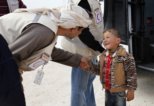 A newly-arrived Syrian refugee boy smiles at an Emirati Red Crescent worker upon his arrival with his family to the new Jordanian-Emirati refugee camp, Mrajeeb al-Fhood, in Zarqa, Jordan, Wednesday, April 10, 2013. A second camp for Syrian refugees has opened in Jordan as more Syrians flee the civil war at home. The Jordanian-Emirati camp is the first funded by the United Arab Emirates and run by its Red Crescent Society in Jordan to assist families, single women, the disabled, and elderly.(AP photo/Mohammad Hannon)