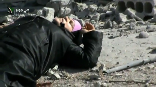 This image taken from video obtained from Shaam News Network, which has been authenticated based on its contents and other AP reporting, shows an injured Syrian woman lying in a street before her rescue by rebels from a firefight in the Jobar neighborhood in Damascus, Syria, Wednesday, April 10, 2013. Syrian President Bashar Assad's troops battled rebels in the outskirts of Damascus on Wednesday and pressed on with a counteroffensive against opposition fighters in the south to prevent their advance on the capital.(AP Photo/Shaam News Network via AP video)