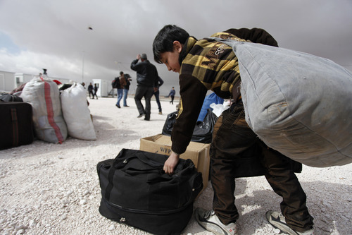 A newly-arrived Syrian refugee boy carries his family's belongings to the new Jordanian Emirate refugee camp, Mrajeeb al-Fhood, in Zarqa, Jordan, Wednesday, April 10, 2013. A second camp for Syrian refugees has opened in Jordan as more Syrians flee the civil war at home. The Jordanian-Emirati camp, is the first funded by the United Arab Emirates and run by its Red Crescent Society in Jordan to  assist families, single women, the disabled, and elderly. (AP photo/Mohammad Hannon)