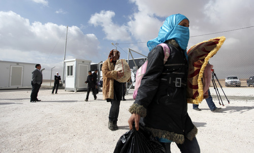 Newly-arrived Syrian refugees carry their belongings upon their arrival to the new Jordanian-Emirati refugee camp, Mrajeeb al-Fhood, in Zarqa, Jordan, Wednesday, April 10, 2013. A second camp for Syrian refugees has opened in Jordan as more Syrians flee the civil war at home. The Jordanian-Emirati camp is the first funded by the United Arab Emirates and run by its Red Crescent Society in Jordan to assist families, single women, the disabled, and elderly.(AP photo/Mohammad Hannon)