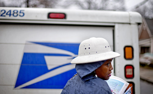 FILE - In this Feb. 7, 2014 file photo, U.S. Postal Service letter carrier Jamesa Euler, delivers mail in the rain in the Cabbagetown neighborhood, in Atlanta. The U.S. Postal Service says it will delay plans to cut Saturday mail delivery because Congress isn't allowing the change. The Postal Service said in February that it planned to cut back in August to five-day-a-week deliveries for everything except packages, as a way to hold down losses. (AP Photo/David Goldman)