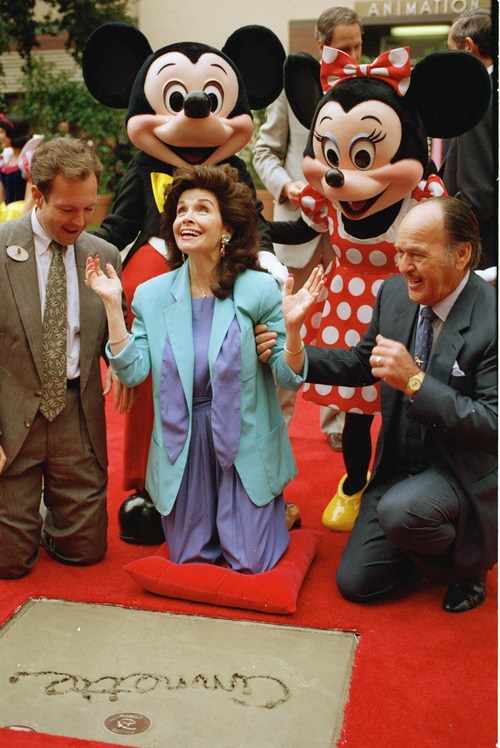 """FILE - In this Oct. 21, 1992 file photo, former """"Mouseketeer"""" Annette Funicello gets set to put her hands in the cement at Walt Disney Studios Theatre, in Burbank, Calif., as she is honored with the Disney Legend Award. With Funicello is her husband, Glen Holt, right, and Jeff Hofman, left, Disney Studios official. Walt Disney Co. says, Monday, April 8, 2013, that Funicello, also known for her beach movies with Frankie Avalon, has died at age 70. (AP Photo/Nick Ut, File)"""