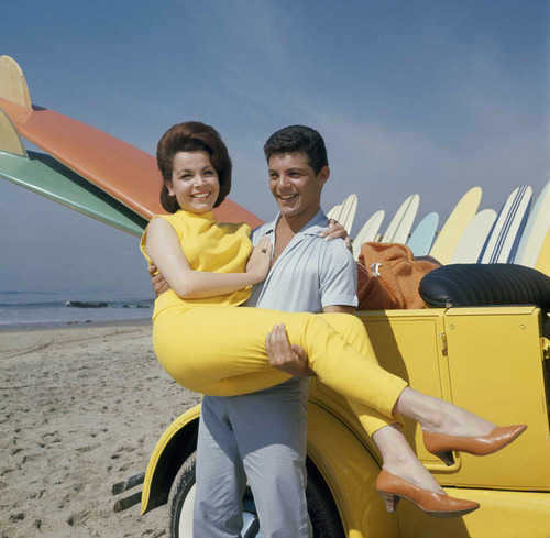 """FILE - In this 1963 file photo, singer Frankie Avalon and actress Annette Funicello are seen on Malibu Beach during filming of """"Beach Party,"""" in California in 1963. Walt Disney Co. says, Monday, April 8, 2013, that former """"Mouseketeer"""" Funicello, also known for her beach movies with Avalon, has died at age 70. (AP Photo/File)"""