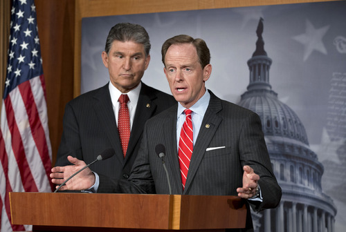 Democratic Sen. Joe Manchin of West Virginia, left, and Republican Sen. Patrick Toomey of Pennsylvania, right, announce that they have reached a bipartisan deal on expanding background checks to more gun buyers, at the Capitol in Washington, Wednesday, April 10, 2013.  (AP Photo/J. Scott Applewhite)