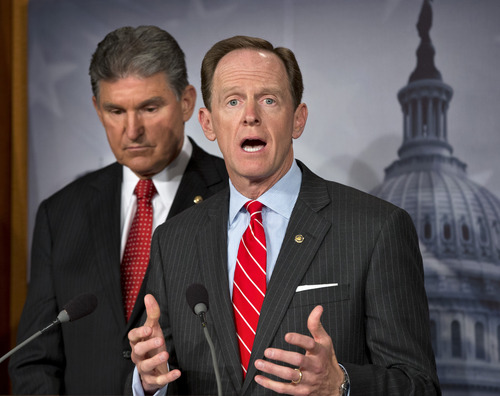 Sen. Joe Manchin, D-W.Va. listens at left, as Sen. Patrick Toomey, R-Pa. announce that they have reached a bipartisan deal on expanding background checks to more gun buyers, Wednesday, April 10, 2013, on Capitol Hill in Washington.  (AP Photo/J. Scott Applewhite)