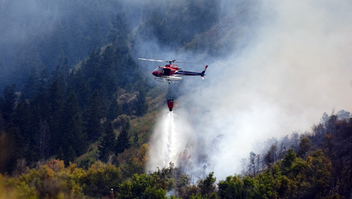 Kim Raff  |  The Salt Lake Tribune Helicopters dump water on a wildfire off U.S. 40 outside of Heber City in Wasatch County on Aug. 19, 2012. State and federal officials are preparing for another busy fire season in 2013.