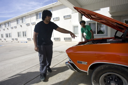Kim Raff  |  The Salt Lake Tribune Kunal Sah, left, looks under the hood of his Chevrolet Chevelle SS396 with his friend Trey Burton under the carport of the front entrance of the Ramada Inn on March 28, 2013. Sah is 19 years old and runs the Ramada Inn in Green River, Utah for his parents, Ken and Sarita Sah, who returned to India after losing a battle with immigration officials seven years ago.