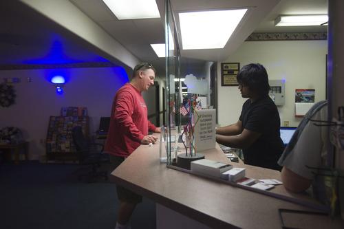 Kim Raff  |  The Salt Lake Tribune Kunal Sah checks in customer Randy Richards at the front desk of the Ramada Inn in Green River on March 28, 2013.