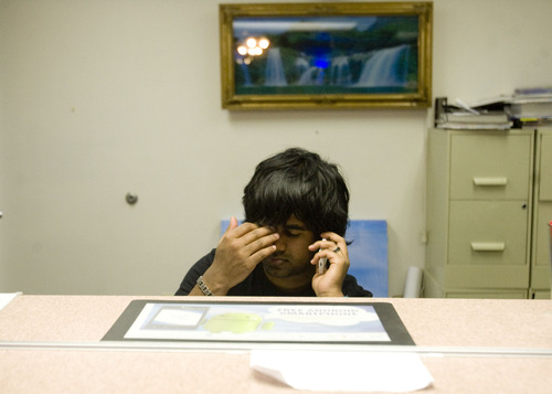 Kim Raff  |  The Salt Lake Tribune While working the front desk, Kunal Sah rubs his head during his nightly phone call to his parents in India at the Ramada Inn in Green River on March 28, 2013. Sah is 19 years old and runs the Ramada Inn for his parents, Ken and Sarita Sah who returned to India after losing a battle with Immigration seven years ago.