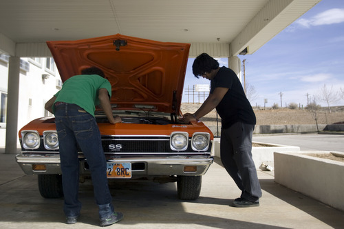 Kim Raff  |  The Salt Lake Tribune Kunal Sah, right, looks under the hood of his Chevrolet Chevelle SS396 with his friend, Trey Burton, under the carport of the front entrance of the Ramada Inn on March 28, 2013. Sah is 19 years old and runs the Ramada Inn in Green River, Utah for his parents, Ken and Sarita Sah, who returned to India after losing a battle with immigration officials seven years ago.
