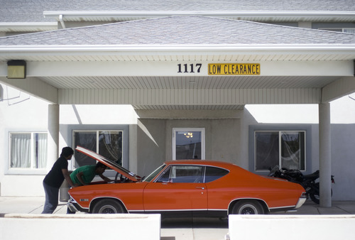 Kim Raff  |  The Salt Lake Tribune Kunal Sah looks under the hood of his Chevrolet Chevelle SS396 with his friend, Trey Burton, under the carport of the front entrance of the Ramada Inn on March 28, 2013. Sah is 19 years old and runs the Ramada Inn in Green River, Utah for his parents, Ken and Sarita Sah, who returned to India after losing a battle with immigration officials seven years ago.