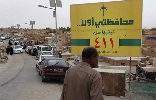 In this picture taken on April 12, 2013, people walk past an election poster at the cemetery in the Shiite holy city of Najaf, 100 miles (160 kilometers) south of Baghdad, Iraq. Voters head to the polls next week for the first time since the U.S. military withdrawal, marking a key test for Prime Minister Nouri al-Maliki's political bloc and for the security forces under his command that are charged with keeping voters safe. (AP Photo/ Alaa al-Marjani)