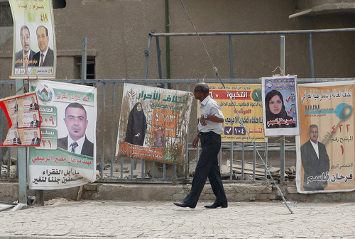A man walks past election posters in Baghdad, Iraq, Saturday, April 13, 2013. Voters head to the polls next week for the first time since the U.S. military withdrawal, marking a key test for Prime Minister Nouri al-Maliki's political bloc and for the security forces under his command that are charged with keeping voters safe. (AP Photo/ Hadi Mizban)