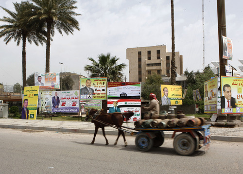 A laborer rides a horse cart carrying cooking gas cylinders passes election posters in Baghdad, Iraq, Saturday, April 13, 2013. Voters head to the polls next week for the first time since the U.S. military withdrawal, marking a key test for Prime Minister Nouri al-Maliki's political bloc and for the security forces under his command that are charged with keeping voters safe. (AP Photo/ Hadi Mizban)