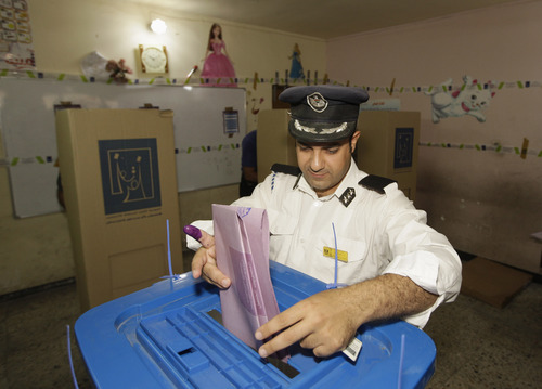 An Iraqi traffic policeman casts his vote during the early voting in for police and army and security forces in Baghdad, Iraq, Saturday, April 13, 2013. Voters head to the polls next week for the first time since the U.S. military withdrawal, marking a key test for Prime Minister Nouri al-Maliki's political bloc and for the security forces under his command that are charged with keeping voters safe. (AP Photo/ Khalid Mohammed)