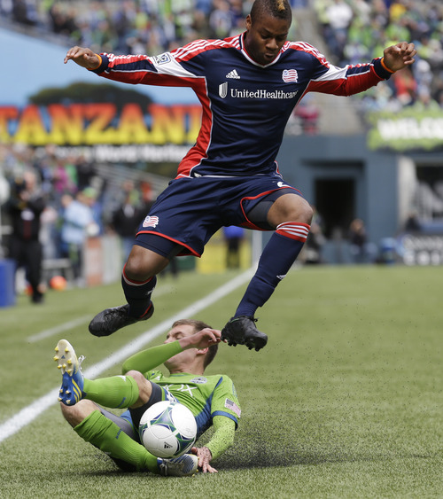 New England Revolution's Andrew Farrell leaps over the sliding challenge from Seattle Sounders' Alex Caskey near the sideline during the first half of an MLS soccer match, Saturday, April 13, 2013, in Seattle. (AP Photo/Ted S. Warren)
