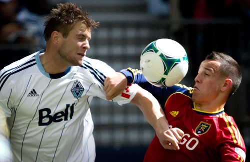 Vancouver Whitecaps' Brad Rusin and Real Salt Lake's Luis Gil vie for the ball during the second half of an MLS soccer game in Vancouver, British Columbia, on Saturday, April 13, 2013. (AP Photo/The Canadian Press, Darryl Dyck)