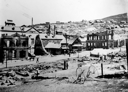 (Salt Lake Tribune Archive)  Pedestrians walk past the remains of Park City's City Hall, with Marsac Mill in the background, after the 1898 fire.