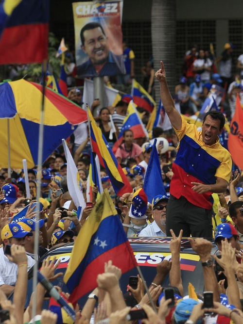 Back dropped by a election poster of Venezuela's President and presidential candidate Hugo Chavez, opposition candidate Henrique Capriles greets his supporters during a campaign rally in Caracas, Venezuela, Sunday, Sept. 30, 2012.  Presidential elections are scheduled for Oct. 7. (AP Photo/Fernando Llano)